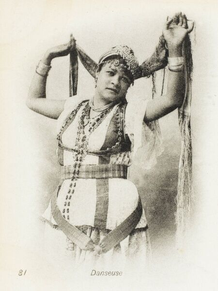 An Algerian Belly Dancer - holding aloft her scarf, in an alluring pose