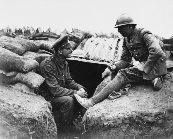 A British soldier in conversation with a French ally in a trench somewhere on the Western Front