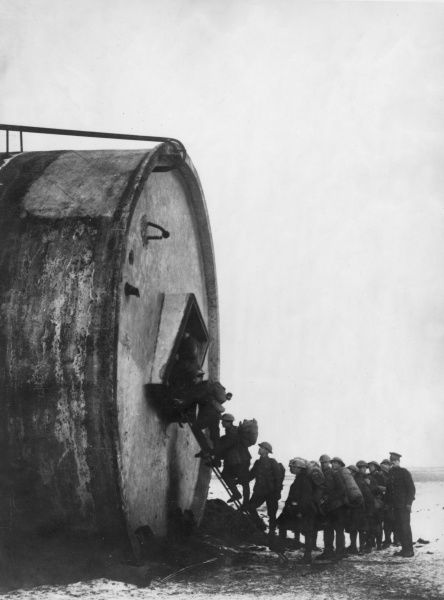Allied soldiers climbing a ladder into what looks like a huge oil drum during the First World War. Date: 1914-1918