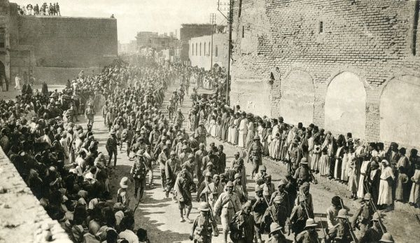 Allied troops marching through Baghdad, Mesopotamia (now Iraq) during the First World War, with Turkish prisoners under escort, and crowds of arab spectators on either side. Date: circa 1917