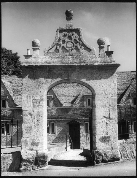 A fine stone archway, leading to a row of picturesque almshouses at Chipping Norton, Oxfordshire, England