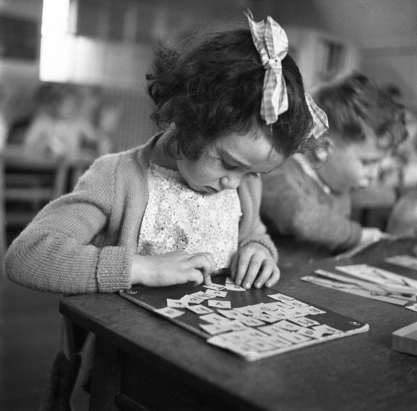 A sweet, studious little girl at Harwich Road Primary, Colchester, with two large plaid ribbons in her hair sits and arranges letters of the alphabet into the words, Father, Mother, Sister, Brother