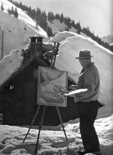 An old man puts the finishing touches to his alpine painting. Date: 1930s
