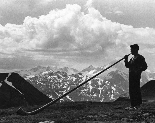 Man blowing a traditional horn in the Alps. Date: 1930s