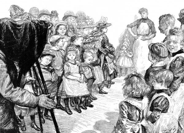 Illustration showing a crowd of East Londoners gathering around an amateur photographer, 1895. At that time, the presence of an affluent photographer keen to take photographs of East End life, brought forth interest and enthusiasm from the locals