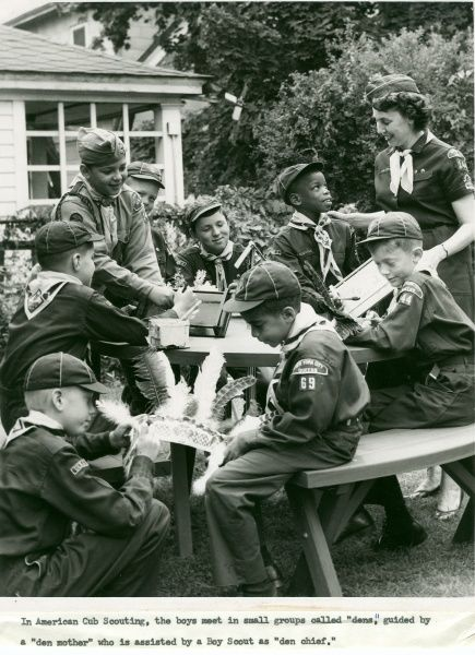 A group of American cub scouts sit around a table doing art and craft activities with their den mother or Akela