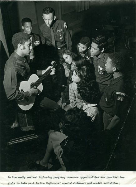 Young men and women sit listening as one of them plays the guitar