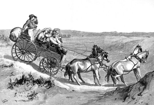 A wagon pulled by four horses crossing uneven ground. The Indians can be glimpsed in the background