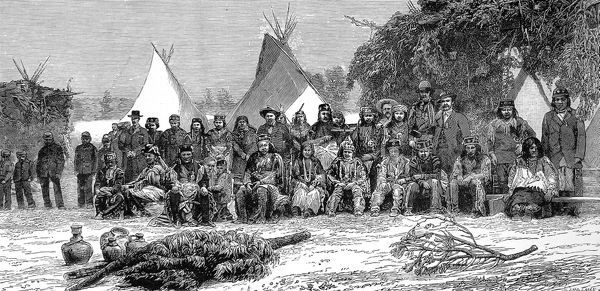 Large group of Apache Indians in a mixture of native and European dress, with wigwams in the background