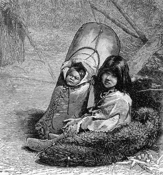 American Indian baby in a papoose and strapped to a cradle board held by young child