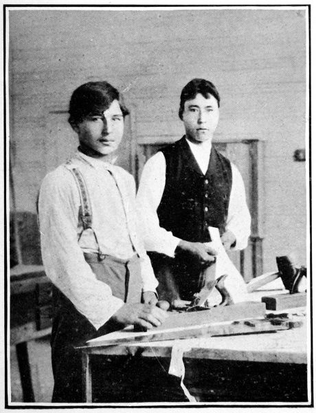 Two young Sioux men using carpenter's tools