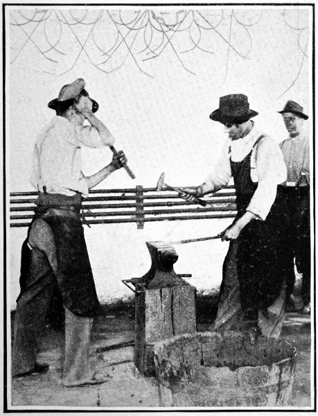Young Sioux men shaping metal on an anvil