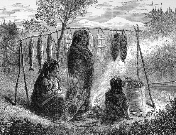 American Indians cooking or drying salmon on a wooden frame over a camp fire