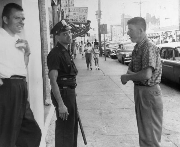 A cop reluctantly has his picture taken whilst on duty outside a bar, Rockaway Beach, Oregon, U.S.A. Date: early 1960s