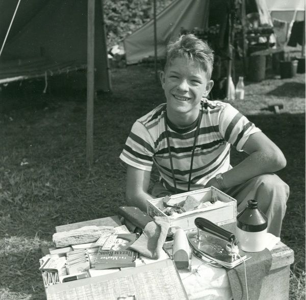An American Boy Scout at a camp crouches behind a table of objects including an iron, a jar and a book about dreams. circa 1950s