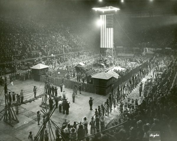 American Scouts gathered in an arena with a full audience. Some of the scouts are dressed up and all are saluting an enormous American flag suspended from the ceiling. circa 1930s