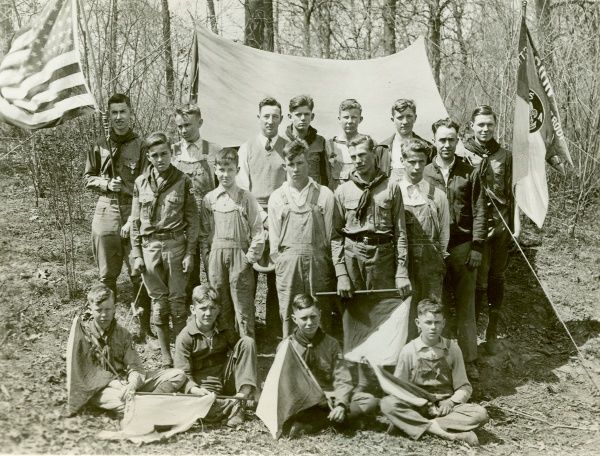 A group of American Scouts pose together in a forest in front of a tent. Some of the boys hold semaphore flags, one boy holds an American flag and one holds a Boy Scouts of America flag. circa 1930s