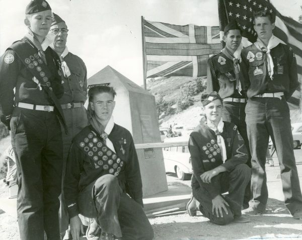 Five American Scouts and a Scout leader stand and kneel in front of a memorial at a Jamboree with both British and American flags flying behind them. circa 1950s