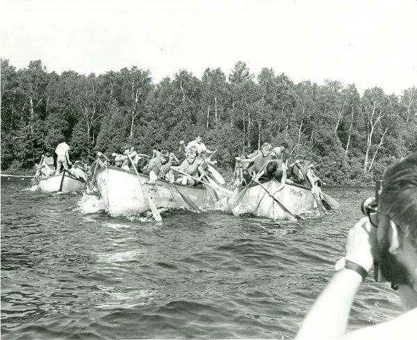 Groups of scouts sit in large boats on a lake and attempt to paddle without crashing into one another. circa 1960s