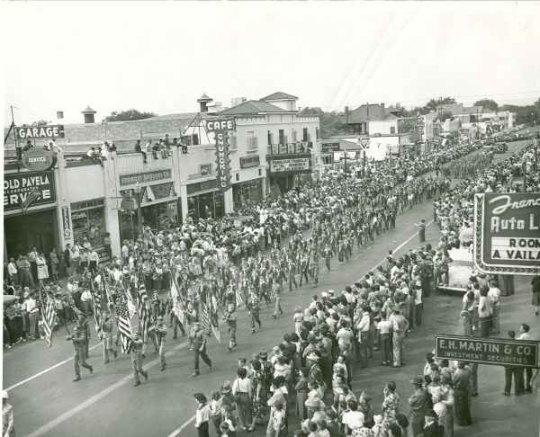 Troops of scouts holding Amerian flags march down a street in a parade at Albuquerque, New Mexico. Residents lines the street to watch. 29 September 1951