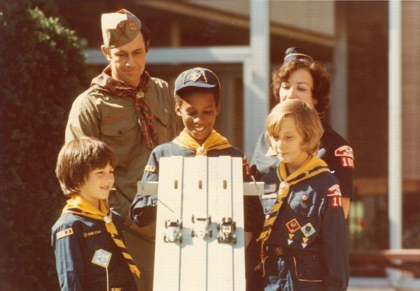 Three American boy scouts and two leaders stand and watch one of them operates a toy car racetrack. circa 1980s