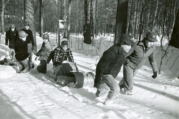 A group of American Boy Scouts dragging a sledge up a steep snow-covered hill in a forest. circa 1950s
