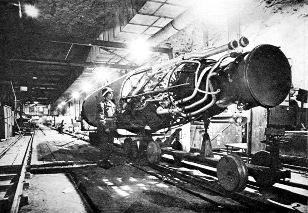 Photograph showing an American soldier of the US First Army studying a partly-assembled German V-2 rocket in an underground assembly plant at Nordhausen, Germany, 1945