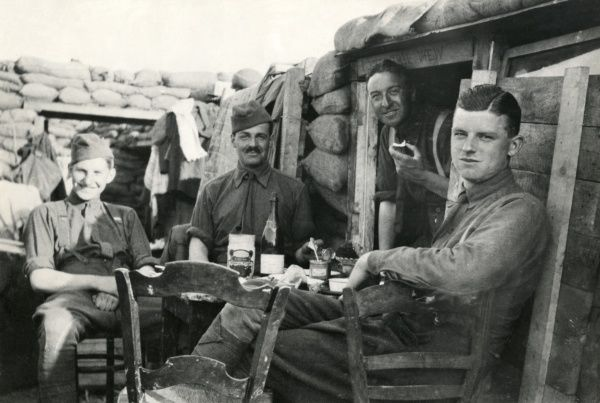 American soldiers relaxing over a meal in a trench on the western front during the First World War. Date: 1917-1918
