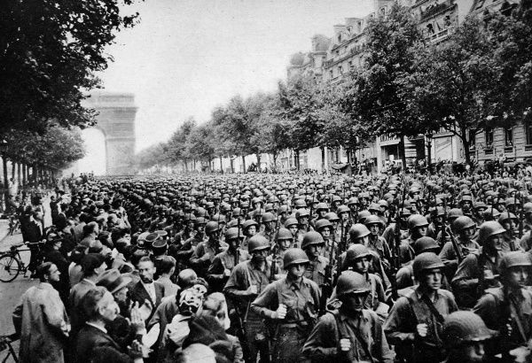 Photograph showing troops of the US Fourth Division marching along the Champs Elysees, Paris, 1944