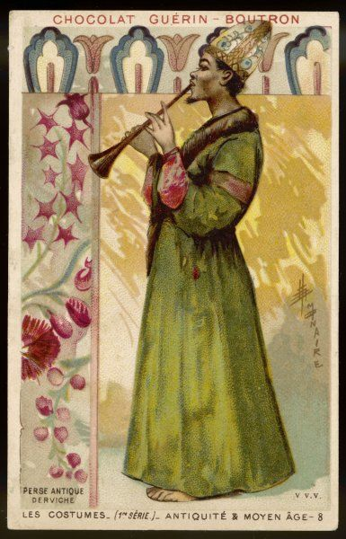 A Dervish of Ancient Persia in long green robe with fur trimming; he wears an ornate hat and plays a woodwind instrument