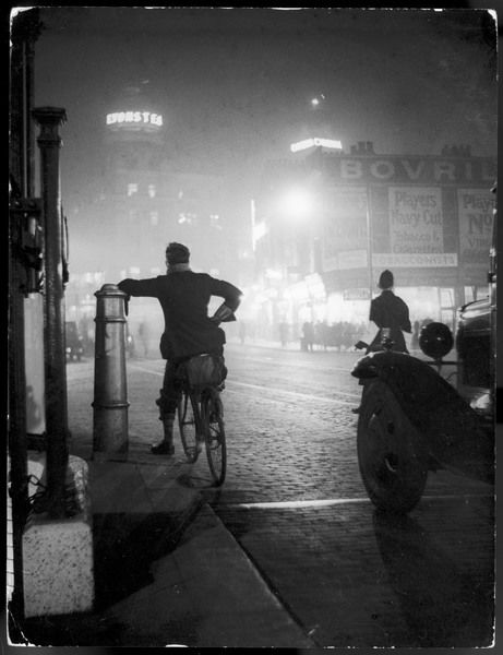 A cyclist stops and takes in the night-time scene as a policeman directs the traffic at the crossroads on Upper Street, the Angel Islington, London