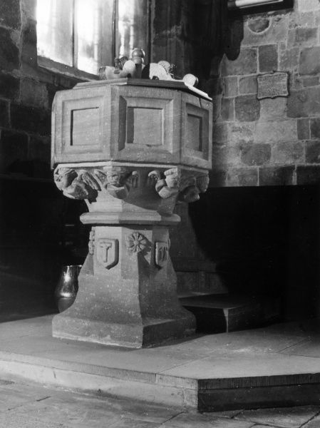 The massive font, with its flying angels corbels below the bowl, in the church at Woodchurch, the Wirral, Merseyside, England. Date: 15th century