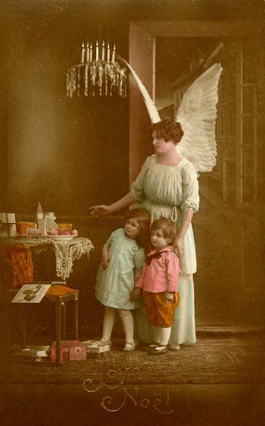 An angel shows two small children their Christmas presents
