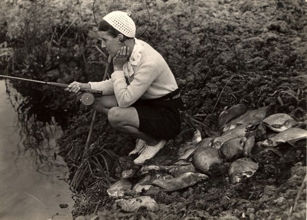 A woman in a very chic outfit for fishing (blouse, cardigan, shorts, white shoes and crocheted beanie hat) sits with her rod beside a pile of fish. Apparently the catch is somewhat fake - all the catch was due to an overstocking on the Norfolk Broads