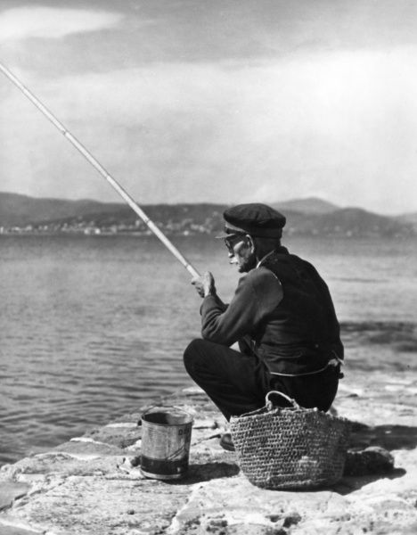 An old man in a peaked cap, fishing at St. Tropez, France. Date: 1930s