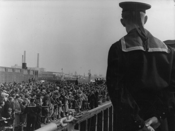 A Russian sailor watching part of the huge crowd waiting to get on board the Soviet ships during the Portsmouth 'Festival of Friendship'. Date: April 1956