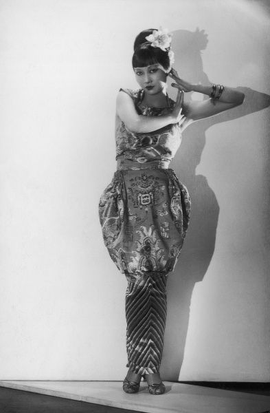Anna May Wong (1905 - 1961), Chinese American film and theatre actress pictured wearing a dress designed by Norman Edwards from a three hundred year old Priest's robe. Taken at the time she was appearing in Cabaret at the Embassy in London