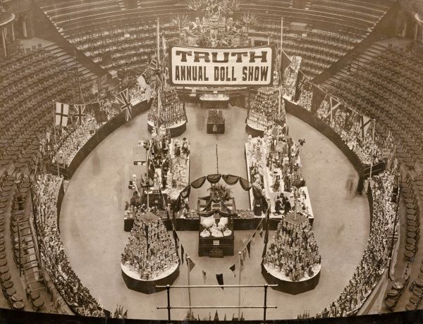 The arena of the Royal Albert Hall, London, set out with a large display of dolls, with empty seats all round. Above the arena is a banner proclaiming TRUTH ANNUAL DOLL SHOW