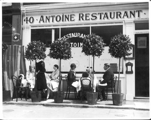 Customers sit outside Antoine's Restaurant, 40 Charlotte Street, Soho, London, and a waitress takes an order