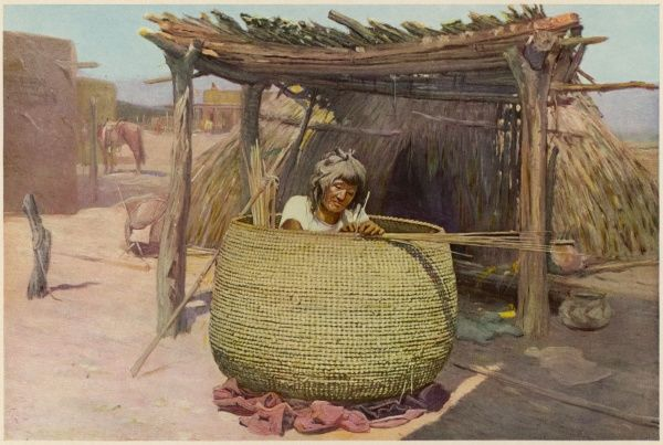 An Apache woman of the American southeast sits inside the basket she is making, weaving it from inside out : it will be used to store grain or vegetables