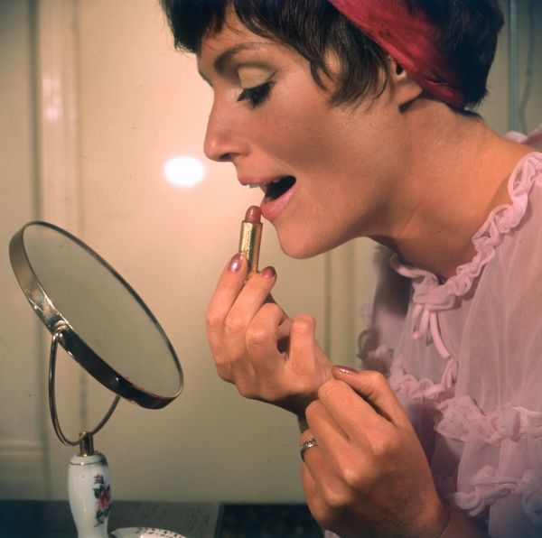 Applying pink lipstick with the aid of a magnifying make-up mirror