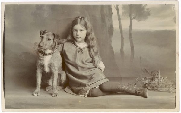 Posed in front of a painted backdrop, a girl and a dog watch the camera apprehensively