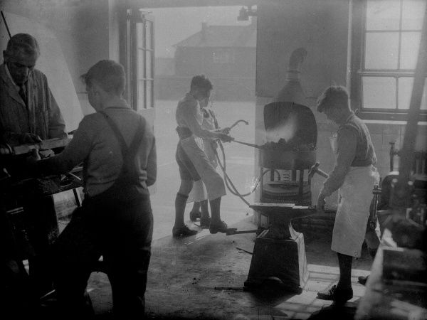Boys, apprentices, learning how to be blacksmiths. Date: early 1930s