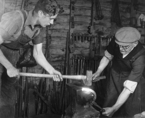 A blacksmith being helped by his apprentice. Date: 1950's