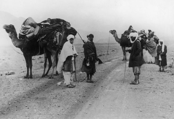 An Arabian camel caravan, some of the men are armed against bandits, on a remote desert road