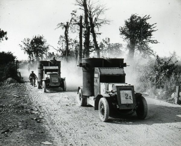 Two armoured cars and a motorcycle outrider on a dusty country road during the First World War