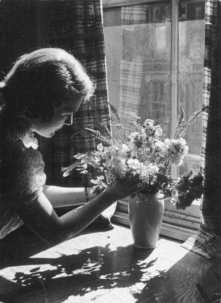 A pretty young woman arranges flowers next to a window on a sunny day