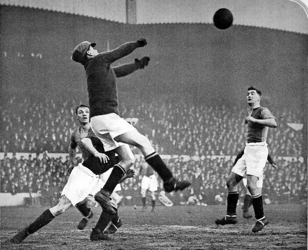 Photograph showing the Mansfield Town goalkeeper jumping highest to punch clear the ball and deny an Arsenal attack during the F.A. Cup fourth round tie at Highbury, 26th January 1929. The match was won 2-0 by Arsenal