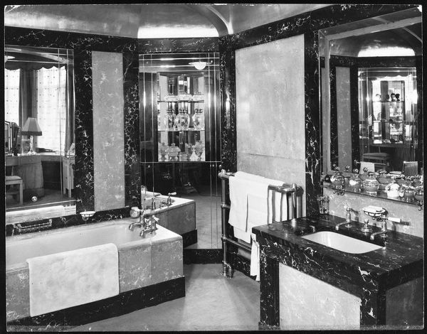 Luxury Art Deco en suite bathroom in various types of marble, with a built-in bathroom cabinet, heated towel rail and stylish taps and fittings
