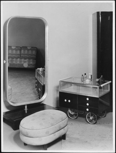 A fine example of how some interiors missed the Art Deco mark! A cumbersome mirror and unattractive pouffe, plus a dreadful drinks trolley which looks like an old pram!